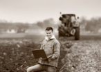 Young landowner with laptop supervising work on farmland, tractor in background, black and white image