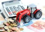 Analyzing financial result in agriculture with tractor pushing a lot of money near office tools