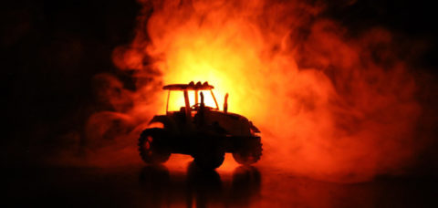 Silhouette of tractor at night with dark foggy background. Toned. Burning vehicle. Decoration